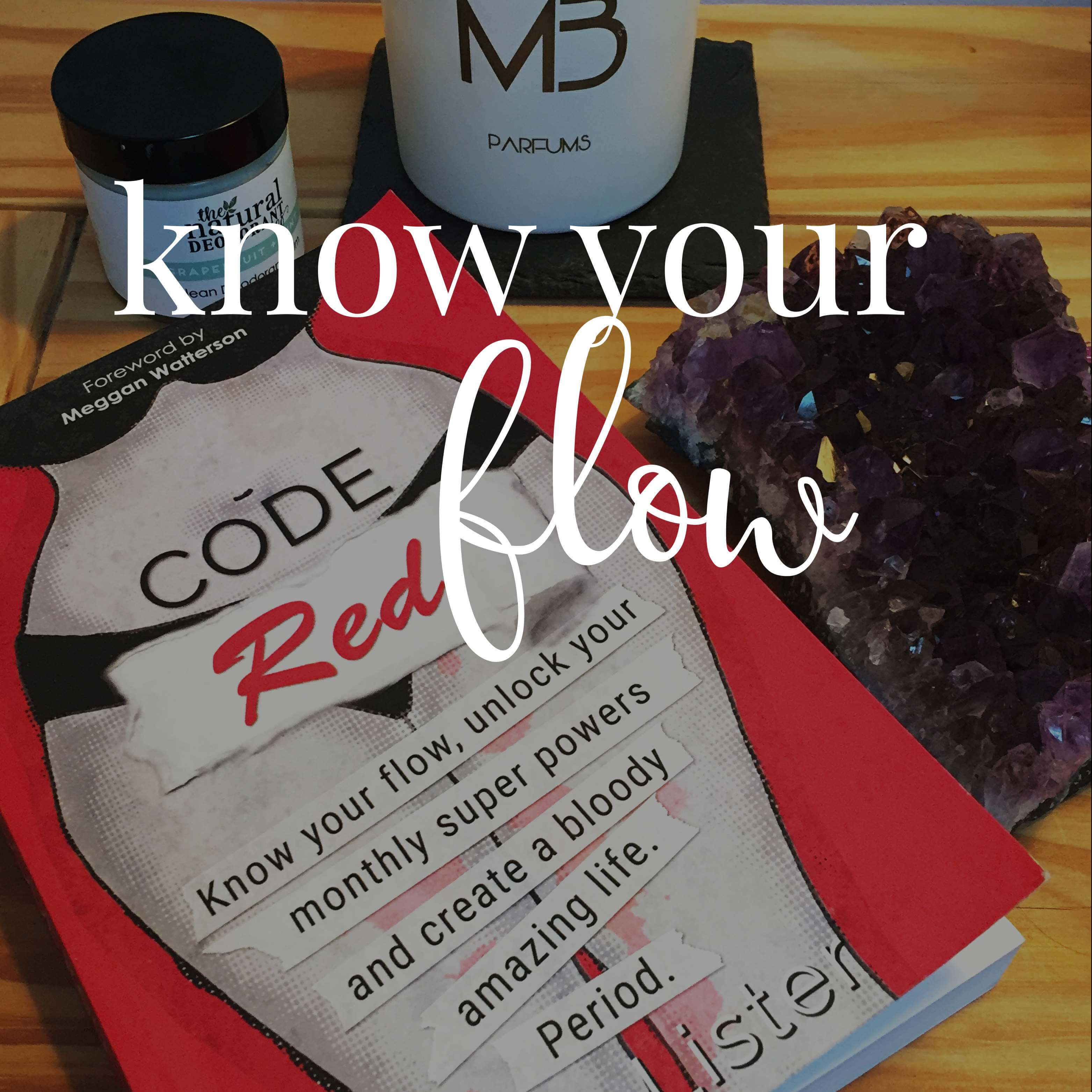 Code red book on wooden surface with amethyst geode, candle and cosmetics.
