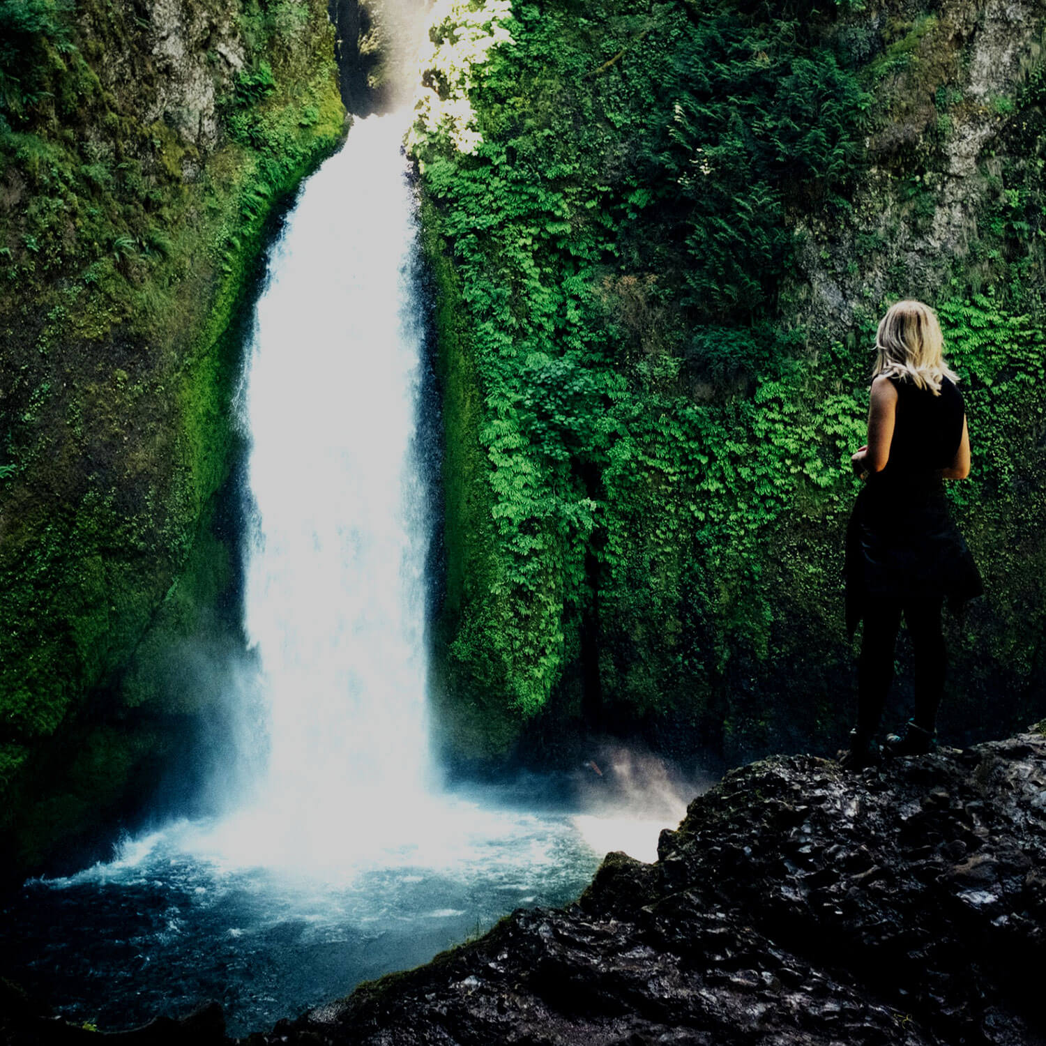 Woman with blonde hair stares at waterfall