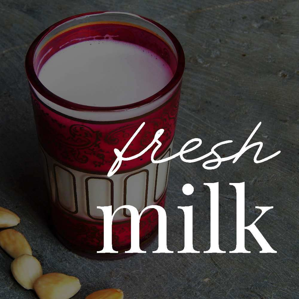 Almond milk in a glass alongside whole almonds