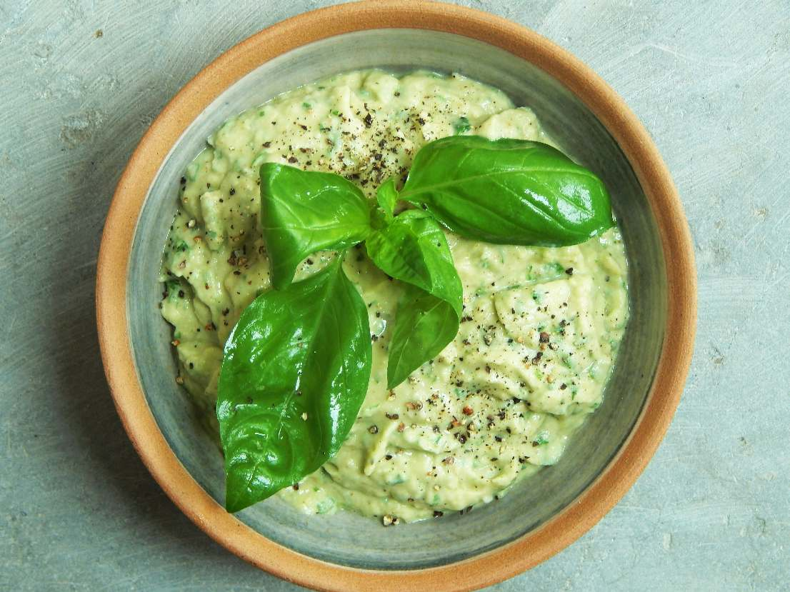 Bowl of hummus decorated with basil leaves