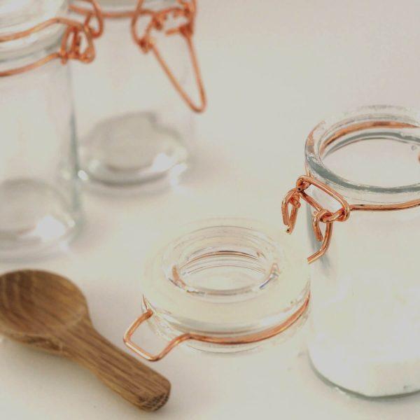 Open glass jar near wooden spoon
