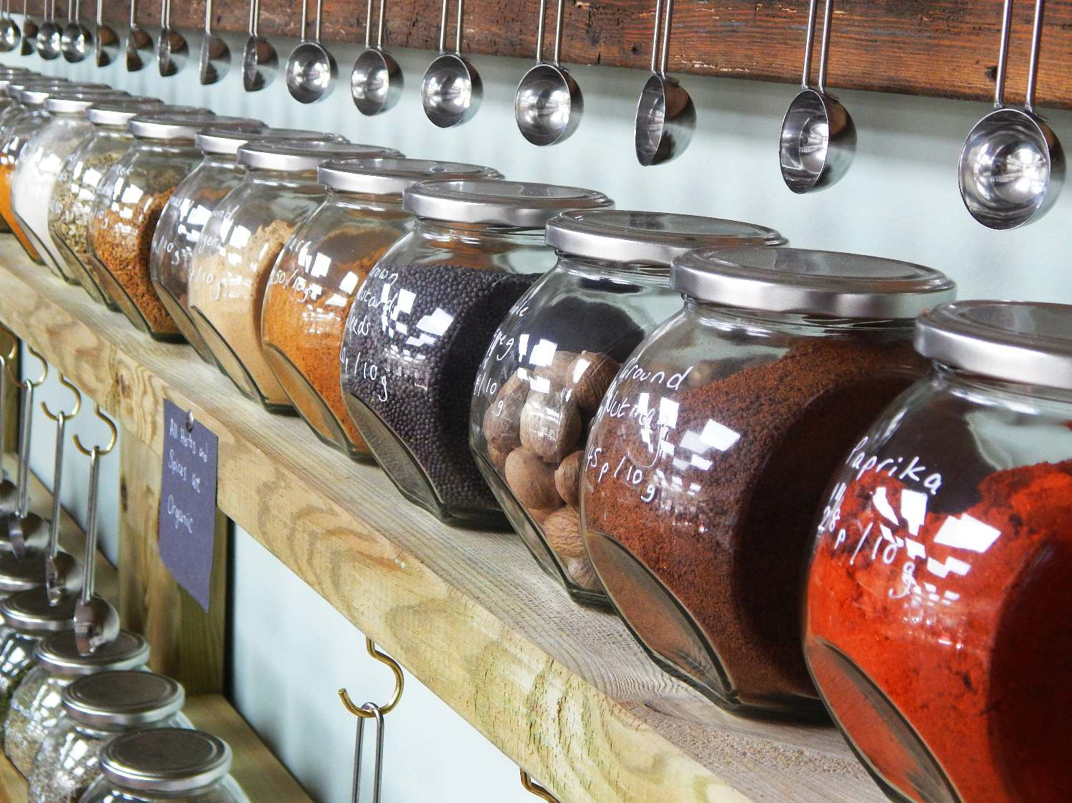 Shelves lined with large jars of spices and seeds