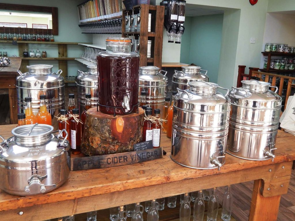 Table loaded with drums of oil and maple syrup, and a large apple cider vinegar dispenser