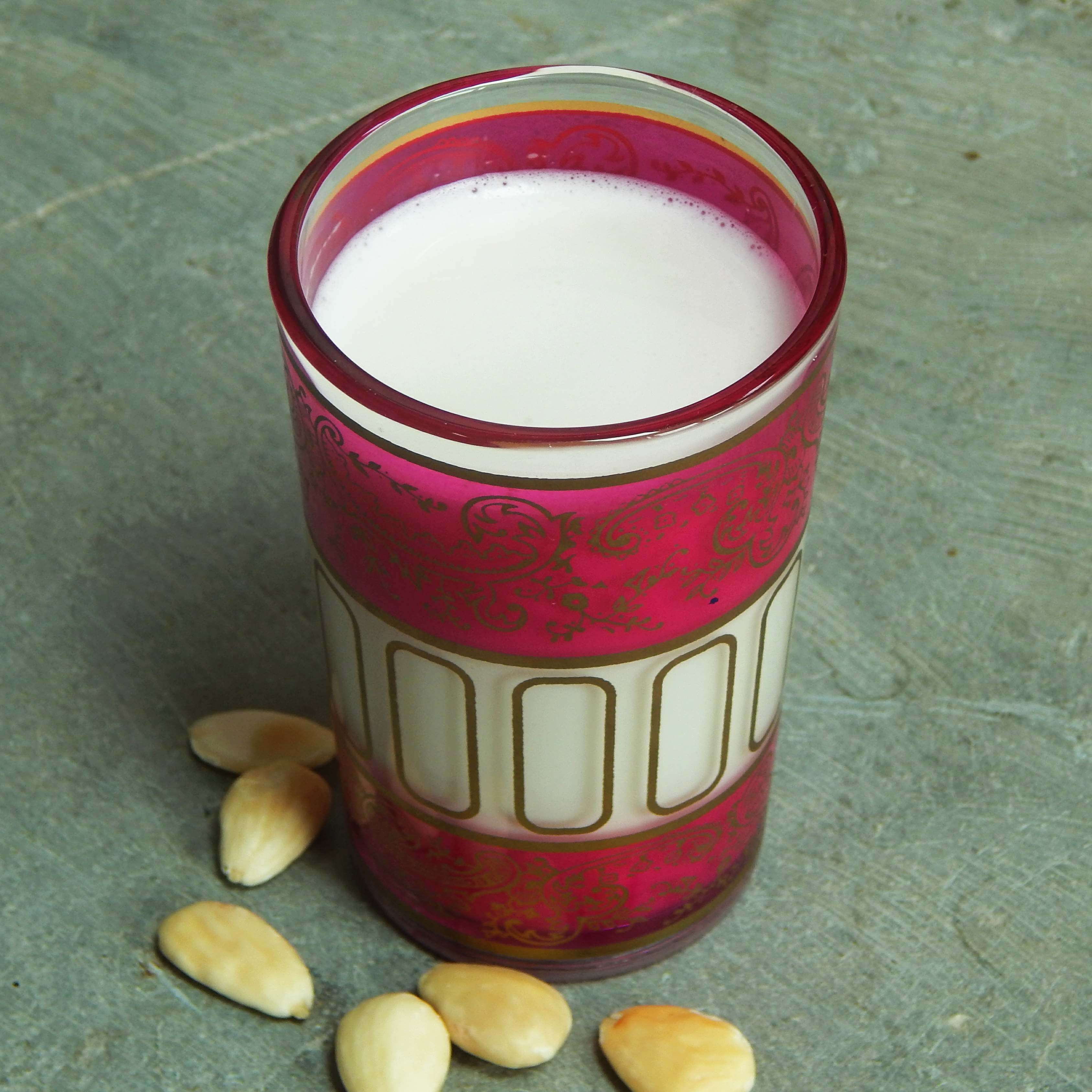 Almond milk in a glass with scattered almonds all around
