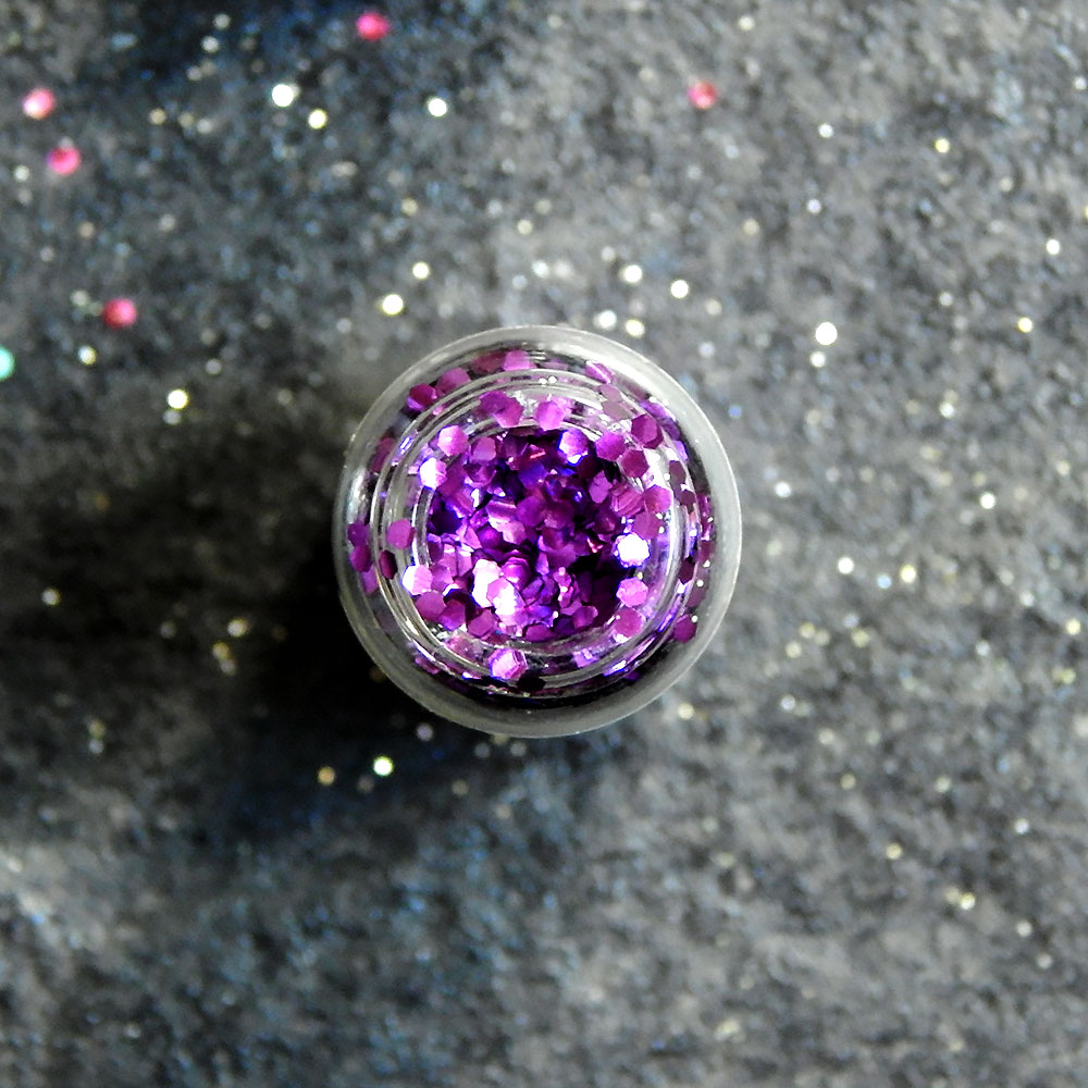 Pot of glitter seen from above, with glitter sprinkled around it