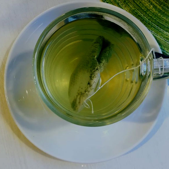 Green tea teabag in a glass cup on a saucer